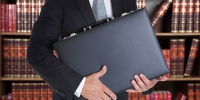 Midsection of businessman holding briefcase in office - Газета Заря